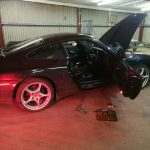 A black car being under our mobile car servicing